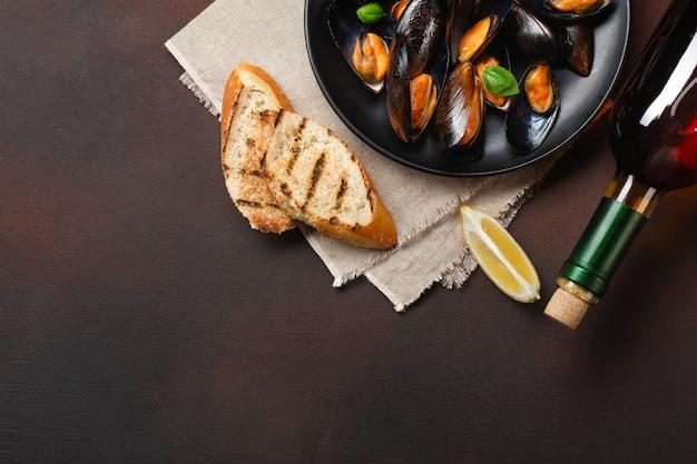 Zeevruchtenmosselen en basilicumbladeren in een zwarte plaat met wijnfles, broodplakken, jute