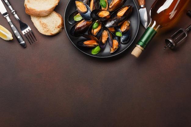 Zeevruchtenmosselen en basilicumbladeren in een zwarte plaat met wijnfles, kurkentrekker, sneetje brood, vork en mes op roestige achtergrond. bovenaanzicht met plaats voor uw tekst.