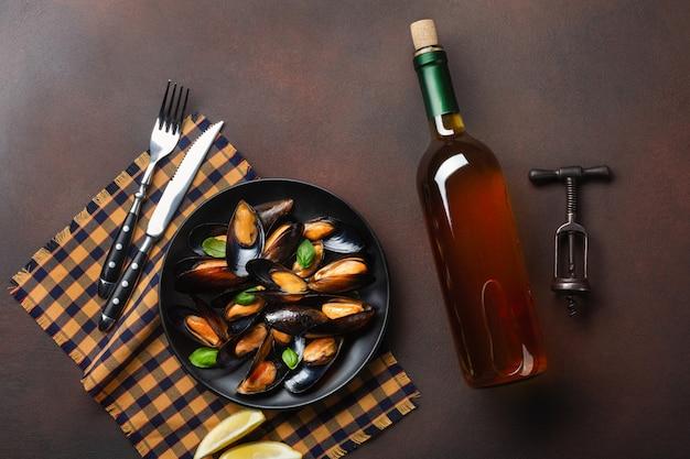Zeevruchtenmosselen en basilicumbladeren in een zwarte plaat met wijnfles, kurketrekker, vork en mes op handdoek