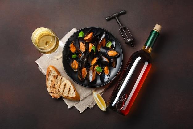 Zeevruchtenmosselen en basilicumbladeren in een zwarte plaat met wijnfles, wijnglas, kurketrekker, broodplakken, jute