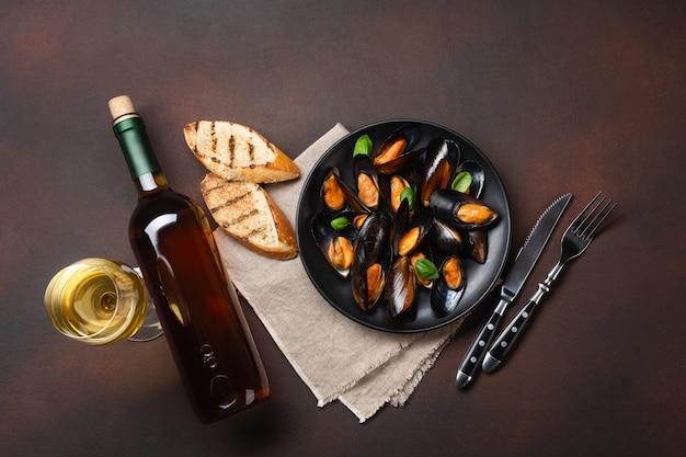 Zeevruchtenmosselen en basilicumbladeren in een zwarte plaat met wijnfles, wijnglas, sneetjes brood, vork, mes, jute op roestige achtergrond. bovenaanzicht.