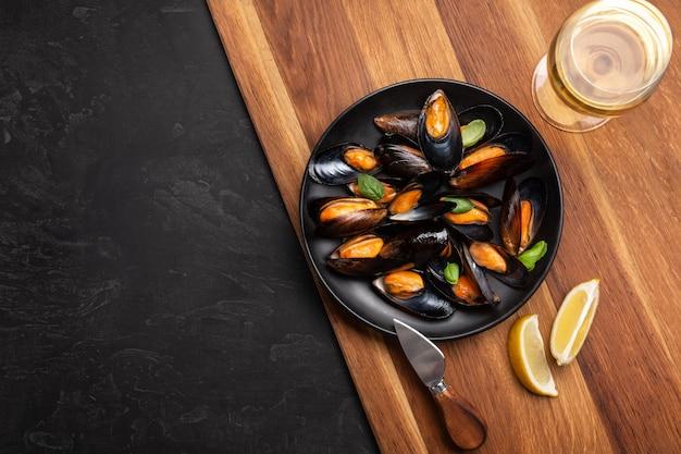 Zeevruchtenmosselen en basilicumbladeren in een zwarte plaat met wijnglas, citroen, mes op houten bord en stenen tafel. bovenaanzicht met plaats voor uw tekst.