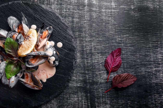 Zeevruchtenmosselen in roomsaus met citroen en basilicum op een steen en een zwarte raad