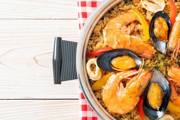 Zeevruchtenpaella met garnalen, kokkels, mosselen op saffraanrijst - spaanse voedselstijl