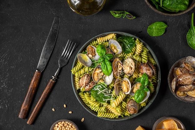 Zeevruchtenpasta met vongole-kokkels, spinazie, parmezaanse kaas, pijnboompitten en basilicum in een bord met vork en mes op zwarte ondergrond