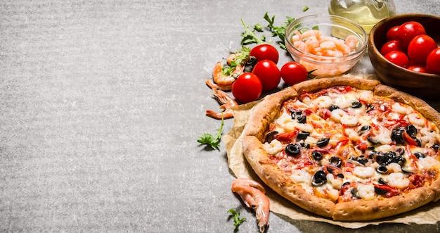 Zeevruchtenpizza met garnalen en tomaten op de steenlijst
