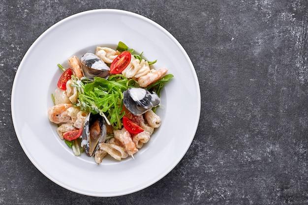Zeevruchtensalade met mosselen, pijlinktvis, garnalen, op een ronde witte plaat, op een grijze ruimte