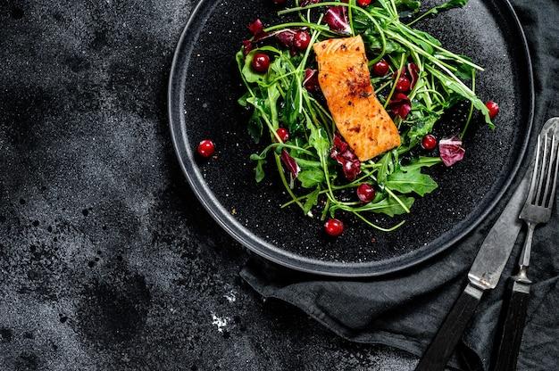 Zeevruchtensalade met zalm, rucola, sla en cranberries. zwarte achtergrond