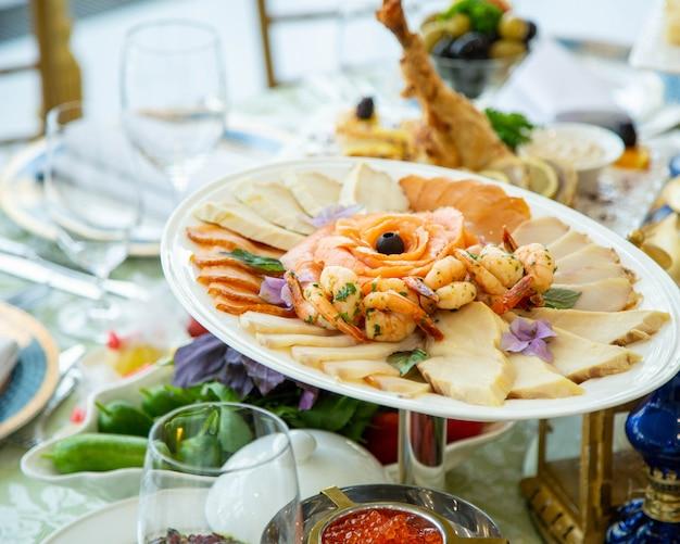 Zeevruchtenschotel met gebakken garnalen, gerookte zalm en andere plakjes vis