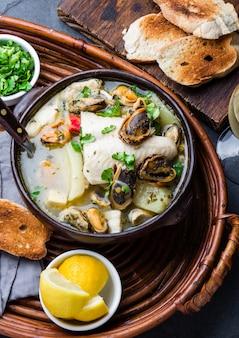 Zeevruchtensoep in kleikommen geserveerd met citroen en koriander.