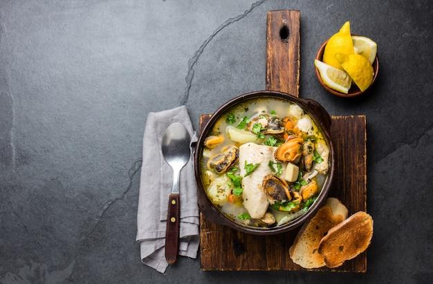 Zeevruchtensoep in kleikommen geserveerd met koude witte wijn.