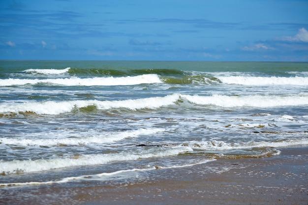 Zeewater, golven en nat zand op strand