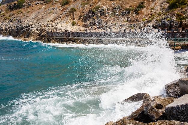 Zeewater slaat tegen rotsachtige rotsen en maakt golven met schuim, ruige pier in de zee