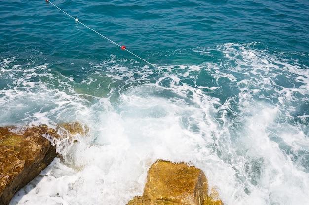 Zeewater slaat tegen rotsachtige rotsen en maakt golven met schuim