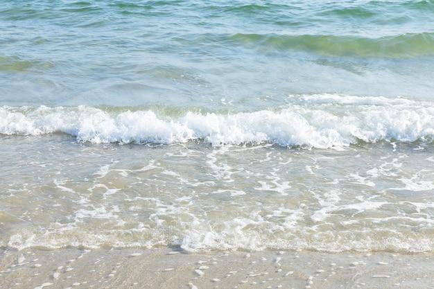 Zeewatergolf met schuim op het strand in zonnige dag