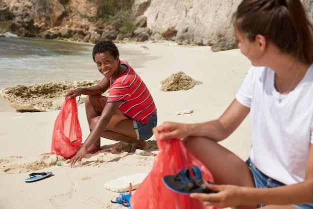 Zeewaterverontreiniging concept. zeg nee tegen rotzooi. onzin en ecologieprobleem. twee drukke tieners recreëren op een tropisch eiland, halen afval op