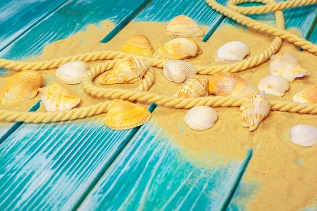 Zeezand en zeeschelpen op blauwe houten vloer
