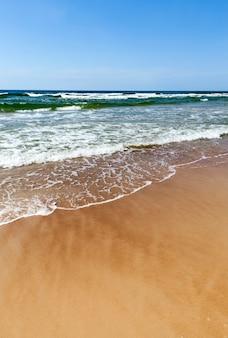 Zeezandstrand met zeegolven die op het zand lopen, de kust aan de oostzee