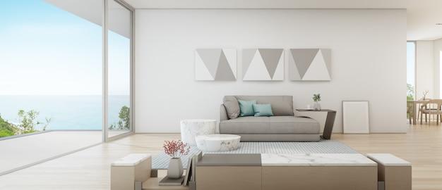 Zeezicht eetkamer en woonkamer van luxe zomer strandhuis met grote glazen deur in de buurt van houten terras.