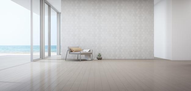 Zeezicht woonkamer van luxe strandhuis met fauteuil in de buurt van de deur op houten vloer.