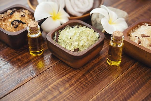 Zeezout, handdoeken, aroma-olie in flessen en bloemen op vintage houten achtergrond.