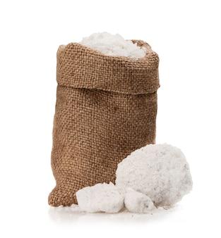 Zeezout in een jutezak op een witte achtergrond.