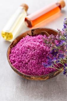Zeezout in kom, aroma-olie in flessen, wellness en bloemen op grijze gestructureerde achtergrond en bloemen op uitstekende houten achtergrond. selectieve aandacht.