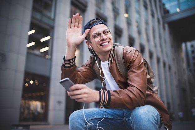 Zeg hallo gelukkige man die iemand ontmoet gelukkige man die naar muziek luistert met een koptelefoon van