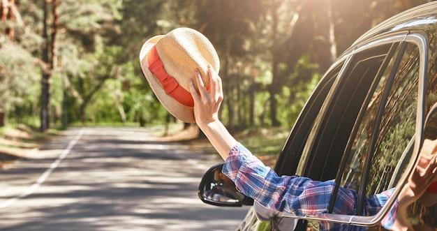 Zeg ja tegen nieuwe avonturen vrouw zwaaiend met een hoed in haar hand terwijl haar