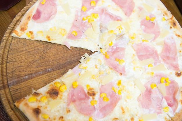 Zeg ja tegen pizza. italiaanse pizza met gesneden plak geserveerd in pizzeria. gekookte pizza met kaas en baconbovenste laagjes. lekker pizza eten. pizza bezorgservice van restaurant naar huis