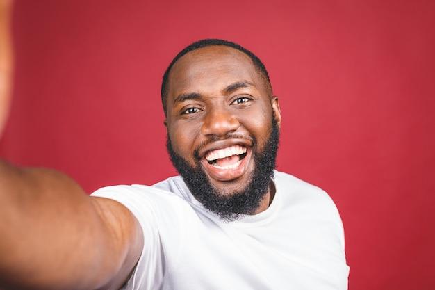 Zeg kaas. sluit omhoog van de jonge mooie donkere zwarte mens in het toevallige glimlachen met tanden, houdend smartphone, makend selfie foto.