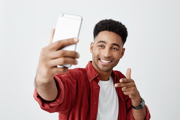 Zeg kaas. sluit omhoog van de jonge mooie donkerhuidige mens met afrokapsel in toevallig wit t-shirt en rood overhemd glimlachend met tanden, houdend smartphone, makend selfie foto.
