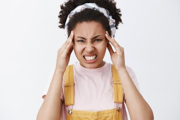 Zeg me niet meer wat ik moet doen. noodlijdende, boos en pissige afro-amerikaanse vrouw in hoofdband en overall, fronsen, tanden op elkaar klemmen, vingers op slapen houden, hoofdpijn voelen of pijnlijke emoties