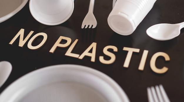 Zeg nee plastic bestek, plastic vervuiling en milieubescherming concept, bovenaanzicht op zwarte achtergrond