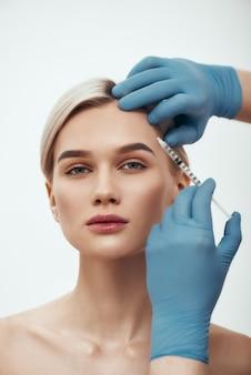 Zeg nee tegen rimpels portret van jonge mooie vrouw die naar de camera kijkt terwijl artsen de hand