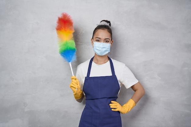 Zeg nee tegen stof. jonge vrouw, schoonmaakster in uniform met medisch masker met kleurrijke microvezelstofdoek en kijkend naar de camera terwijl ze tegen een grijze muur staat. schoonmaakdiensten tijdens pandemie