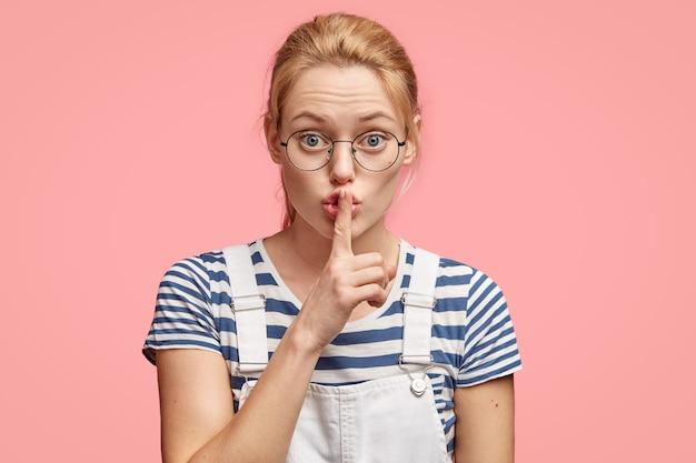 Zeg niets meer! mooie serieuze europese vrouw maakt zwijg gebaar, houdt de wijsvinger op de lippen, vraagt om stil te zijn