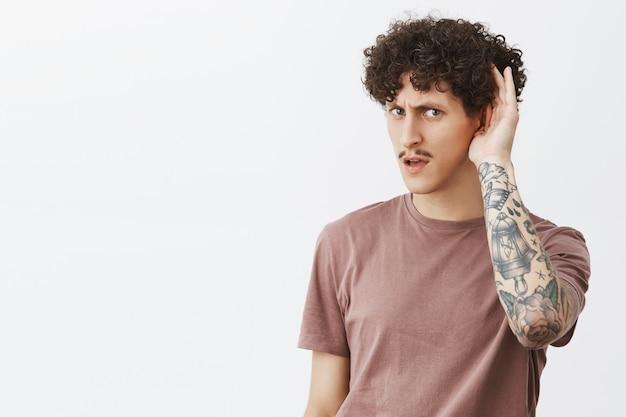 Zeg nogmaals, kan niet duidelijk horen. portret van intense stijlvolle knappe jonge man met krullend kapsel, snor en getatoeëerde arm met hand in de buurt van oor vragen om vraag gazign gericht te herhalen