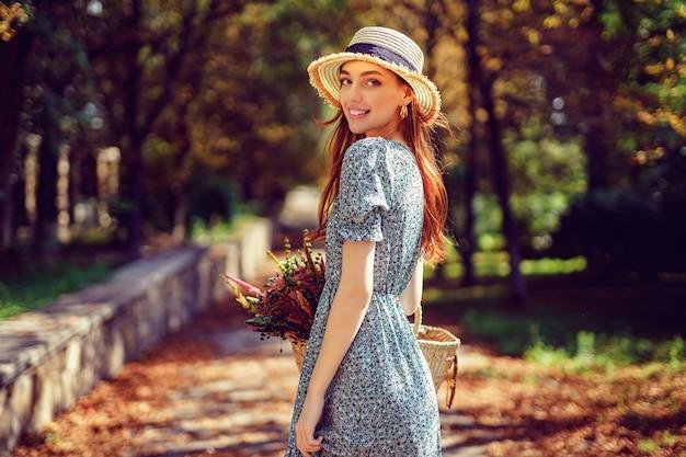 Zegen roodharig meisje loopt alleen in het herfstpark op een zonnige warme dag terwijl ze in de zomer een handtas vasthoudt