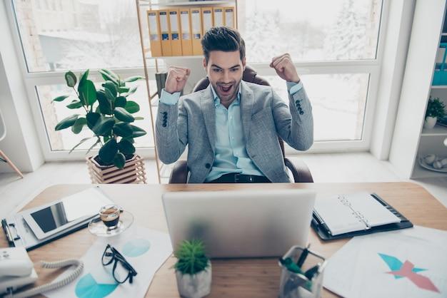 Zegevierend man in pak werken bij bureau