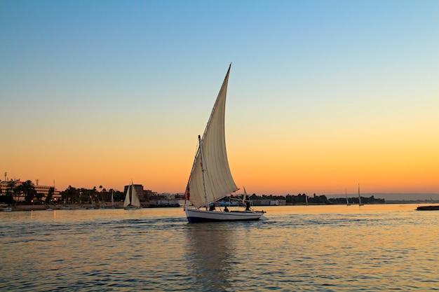 Zeilboot bij zonsondergang in de nijl, egypte