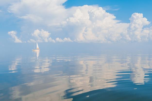 Zeilboot in zee in zonnige dag met wolken weerspiegeld in het water.