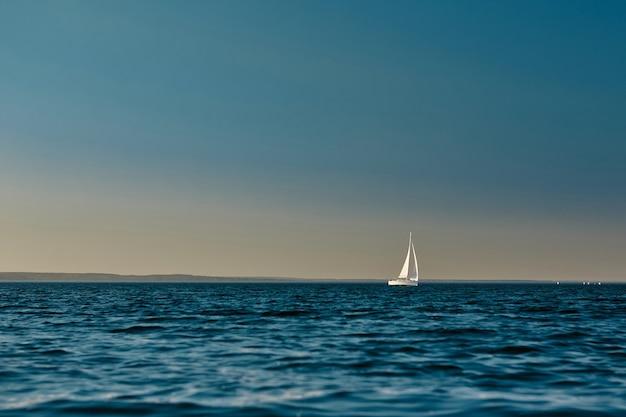 Zeilboot of jacht met open witte zeilen drijvend op de zee bij zonsondergang majestueus landschap kalm