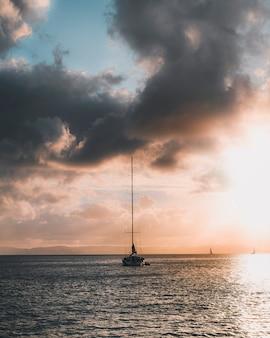 Zeilboot onder een pastelkleurige hemel