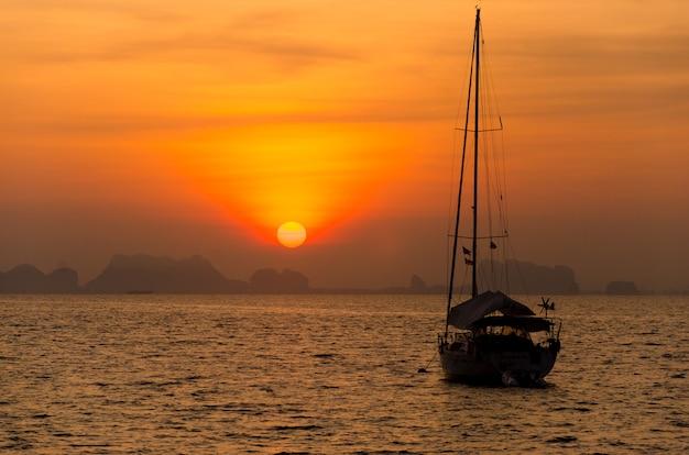 Zeilbootoverzees in het avondzonlicht over mooie grote bergen, de zomeravontuur phuket