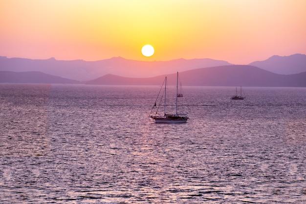 Zeilboten bij zonsondergang. prachtige zee zonsondergang achtergrond.