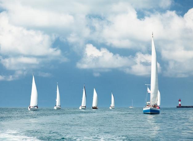 Zeilboten zeilen, blauwe wolkenlucht en witte zeilen
