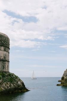 Zeiljacht op zee zeilen op de achtergrond fort bokar op de muren van de oude stad van dubrovnik