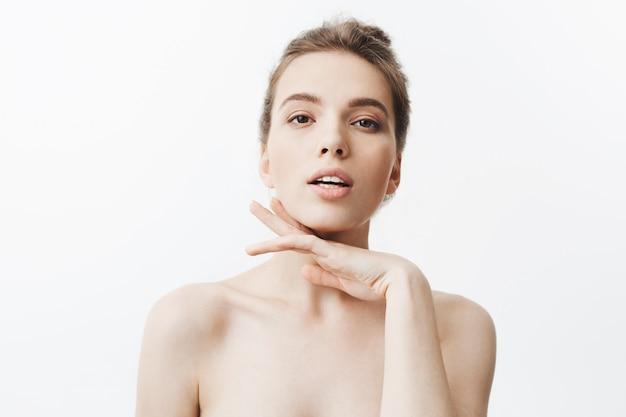 Zeker aantrekkelijk jong donkerharig kaukasisch meisje met knotkapsel en naakte schouders die hand onder kin met flirterige gezichtsuitdrukking en geopende mond houden.