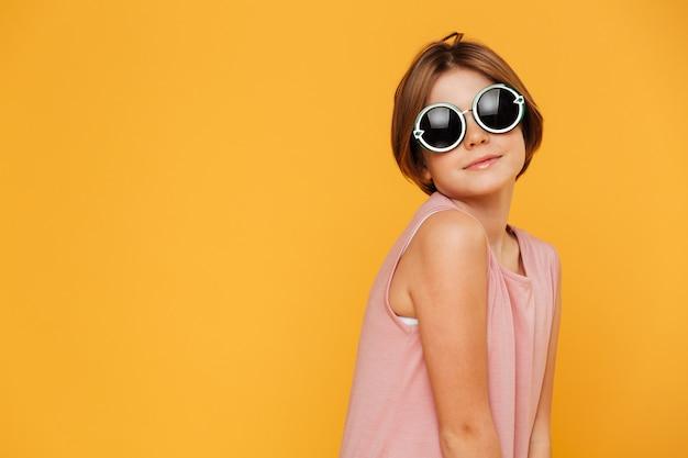 Zeker ernstig meisje dat in zonnebril opzij kijkt